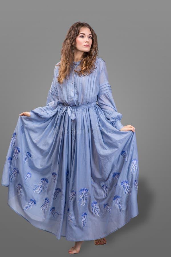 Mädchen im blauen Kleid der Matrizenpappe mit Stickerei stockbild