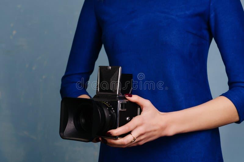 Mädchen im blauen Kleid der Weinlese, das alte mittlere Formatkamera hält stockfoto
