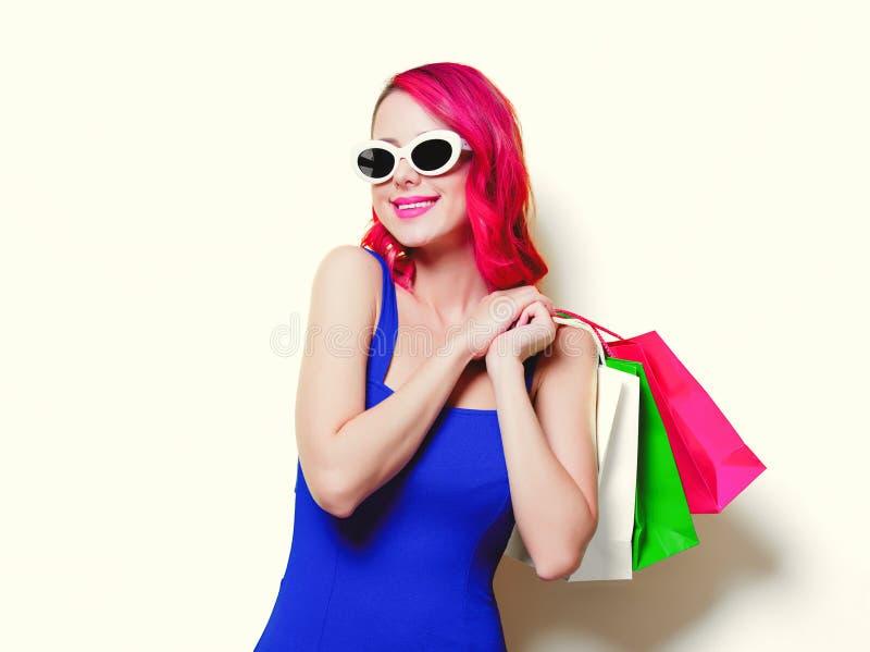 Mädchen im blauen Kleid mit farbigen Einkaufstaschen stockfoto