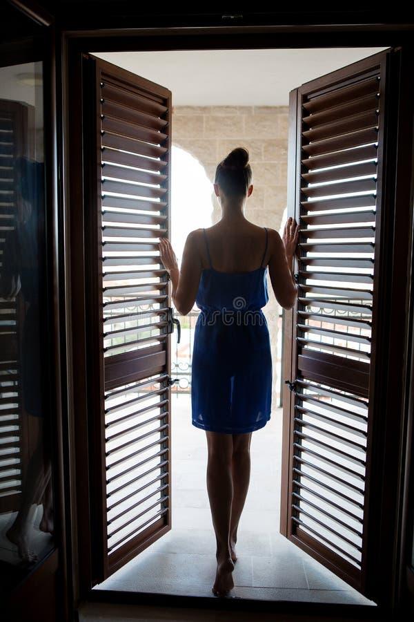 Mädchen im blauen Kleid steht im Eingang stockbild