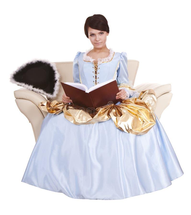 Mädchen im blauen lond Kleid mit Buch auf Stuhl. lizenzfreies stockbild