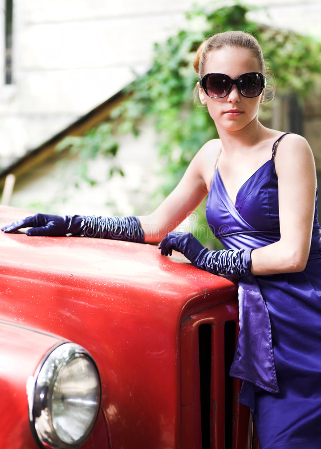 Mädchen im blauen nahen roten Auto lizenzfreie stockfotos