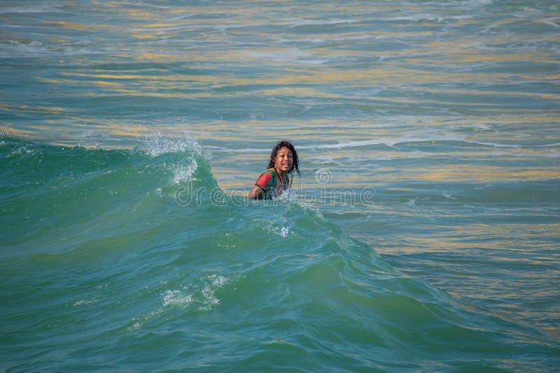 Mädchen im bunten Kleid die Wellen genießend lizenzfreies stockbild