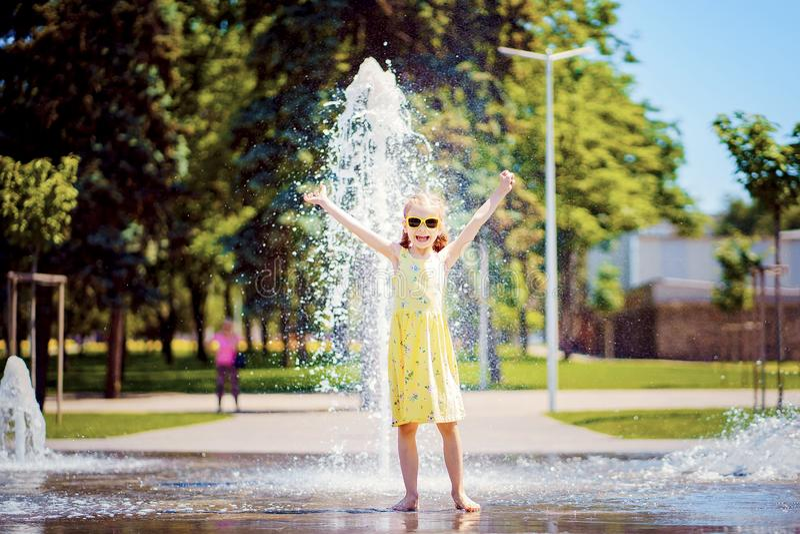 Mädchen im gelben Kleid, das Spaß den Spray des Brunnens genießend spielt und hat stockbilder