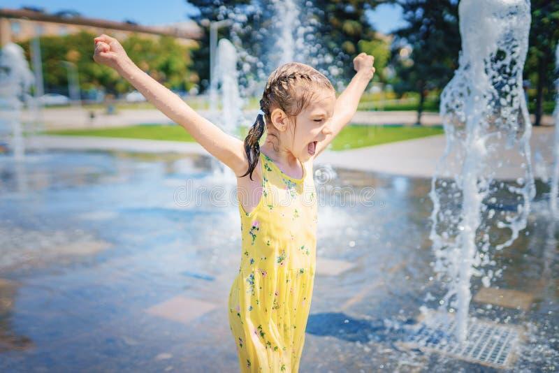 Mädchen im gelben Kleid, das Spaß den Spray des Brunnens genießend spielt und hat stockbild