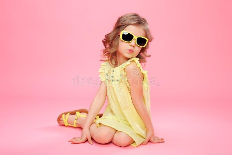 Mädchen im gelben Kleid und in der Sonnenbrille lizenzfreies stockfoto