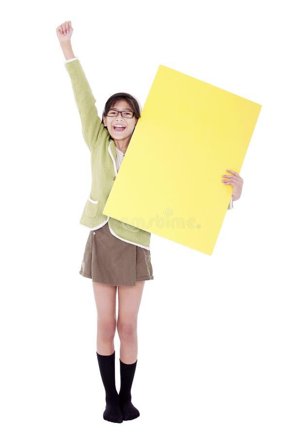Mädchen im grünen Strickjacke holidng Leerzeichen-Gelbzeichen, Arm herein zujubelnd stockfoto