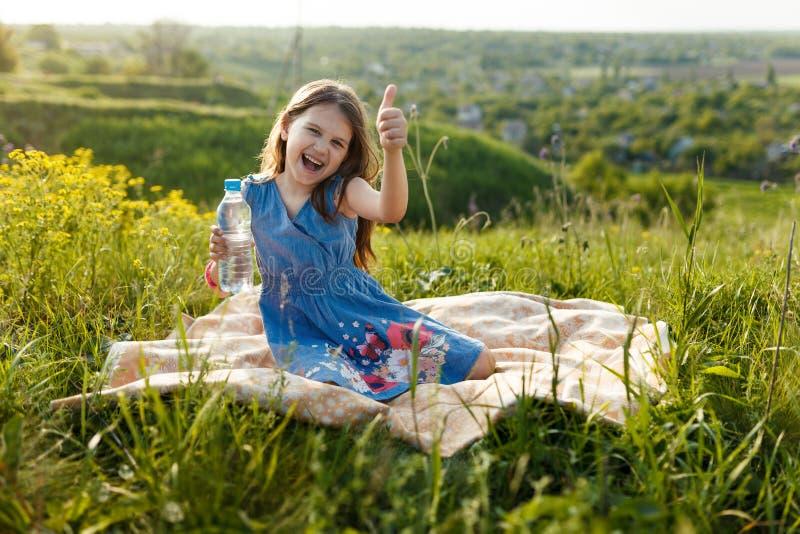 Mädchen im Gras mit Plastikwasserflasche lizenzfreies stockfoto