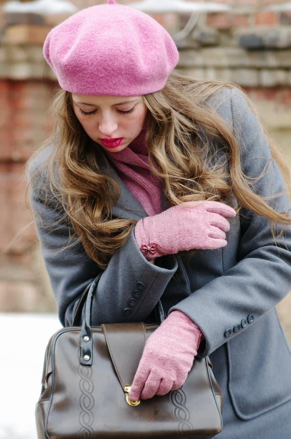 Mädchen im grauen Mantel und im rosa Barett, öffnet die Tasche lizenzfreie stockfotografie