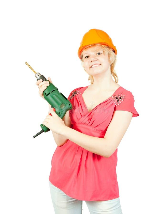 Mädchen im harten Hut mit Bohrgerät lizenzfreie stockbilder
