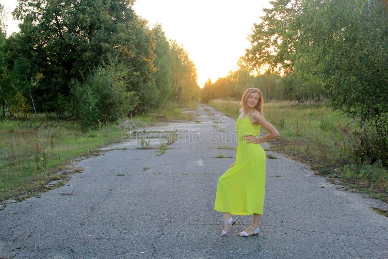 Mädchen im hellen gelben Kleid am Abend draußen stockbild