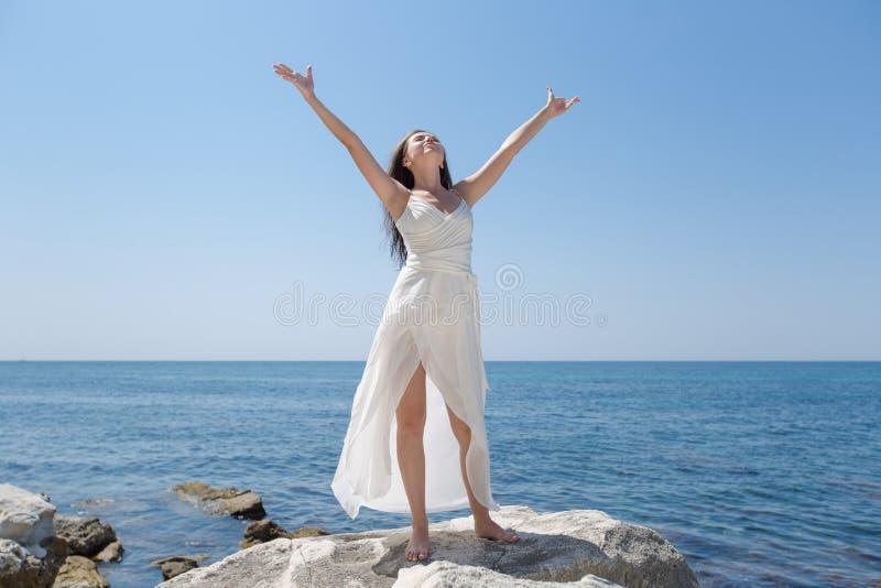 Mädchen im Hochzeitskleid, das gegen Meer mit den Armen ausgestreckt aufwirft stockfoto