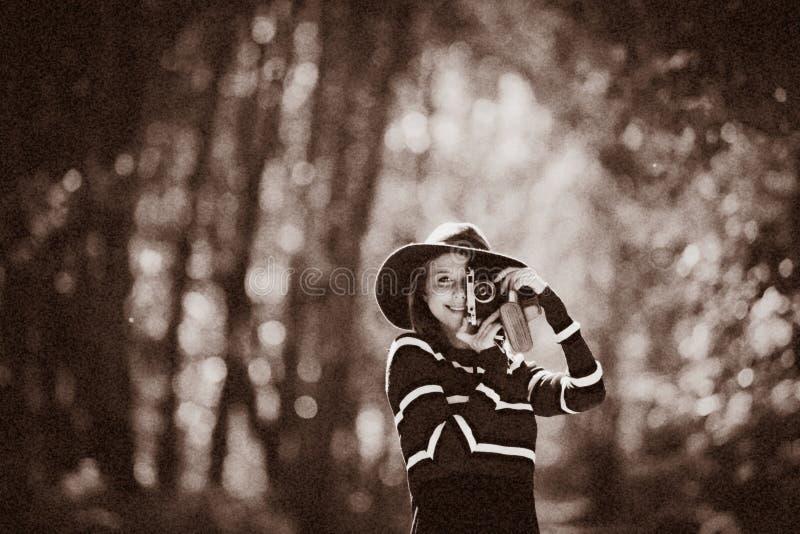 Mädchen im Hut mit einer Kamera im Herbstpark lizenzfreies stockfoto