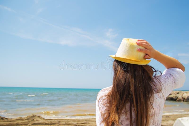 Mädchen im Hut sehen auf dem Meer stockbild