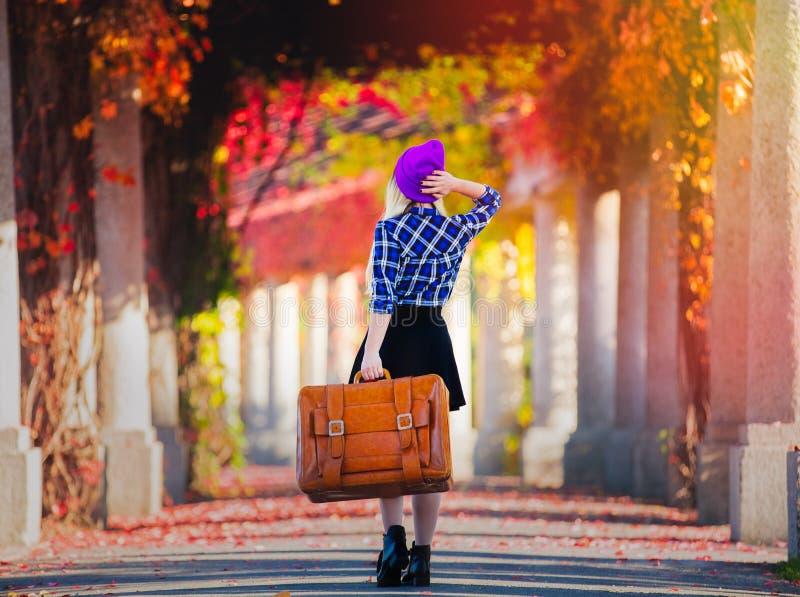 Mädchen im Hut und im Hemd mit Koffer in der Gasse der roten Traube stockfotos