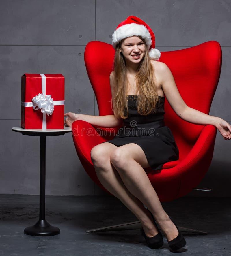 Mädchen im Hut von Santa Claus auf Weihnachtsgeschenken stockbild