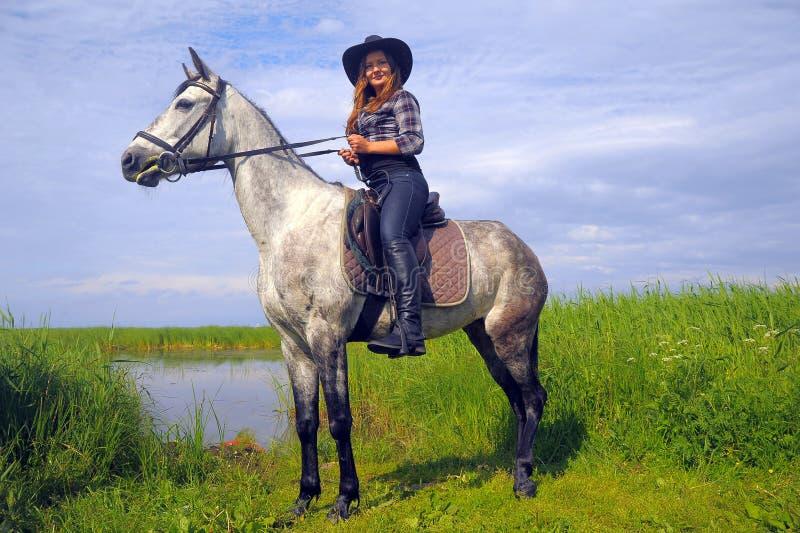 Mädchen im karierten Hemd und in Cowboyhut, die ein Pferd reiten stockbild