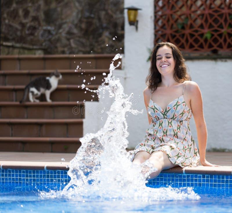 Mädchen im Kleid, das nahe Pool stillsteht lizenzfreie stockfotos