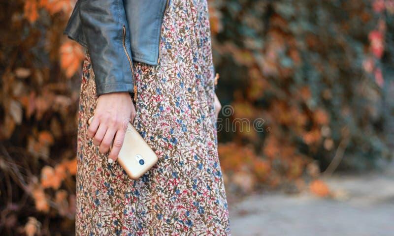 Mädchen im Kleid hält das Telefon lizenzfreie stockfotos