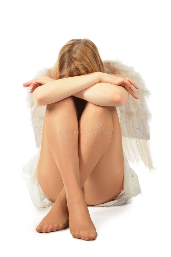 Mädchen im Kostüm des Engels sitzt Gesicht in den Knien stockfotos