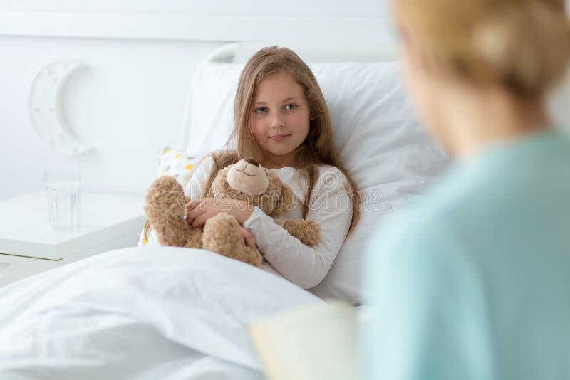Mädchen im Krankenhaus, das einen Teddybären hält stockfotos