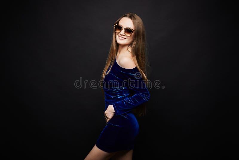 Mädchen im kurzen blauen Kleid und in den Gläsern auf schwarzem Hintergrund lizenzfreies stockbild