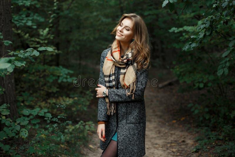 Mädchen im Mantel mit einem Schal im Park auf einem Hintergrund von Büschen lizenzfreies stockfoto