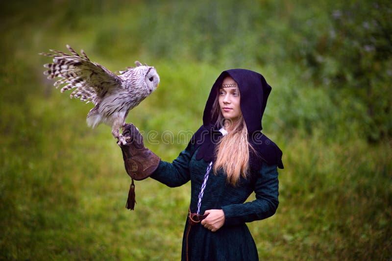Mädchen im mittelalterlichen Kleid hält eine Eule auf ihrem Arm lizenzfreie stockbilder