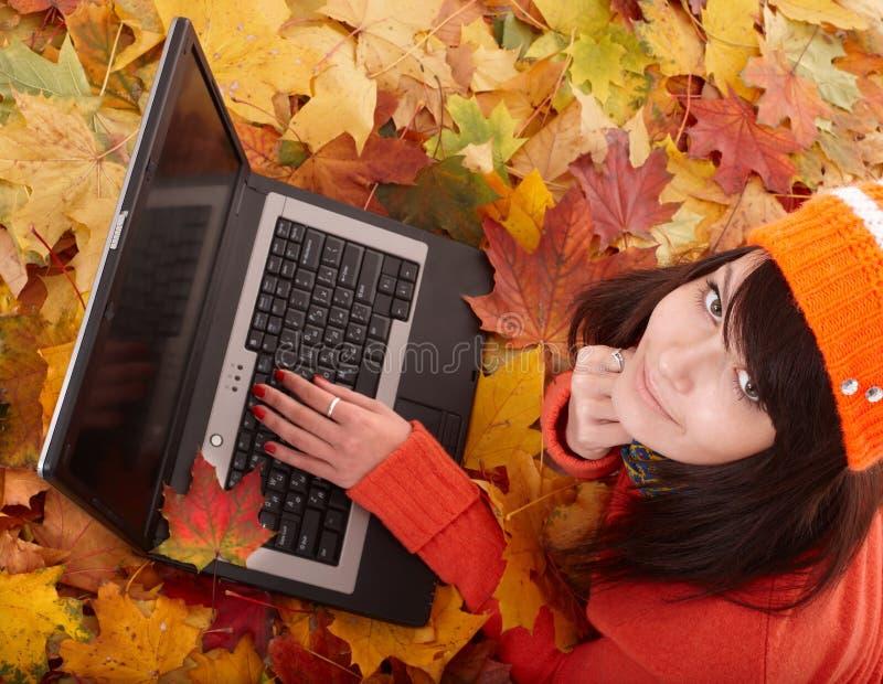 Mädchen im orange Laub des Herbstes mit Laptop. lizenzfreies stockfoto