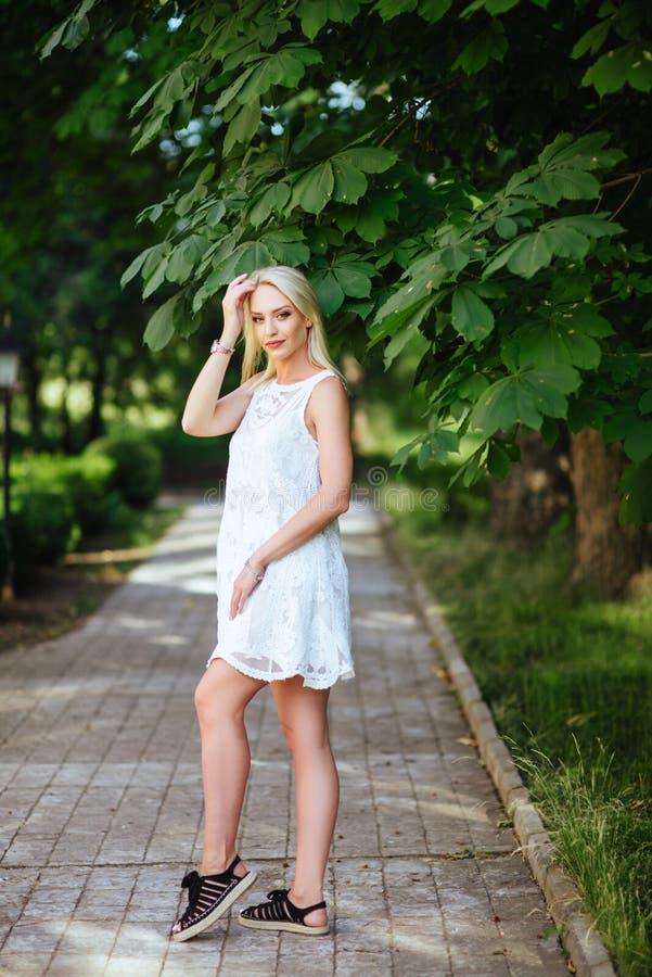 Mädchen im Park in einem weißen Kleid stockbild