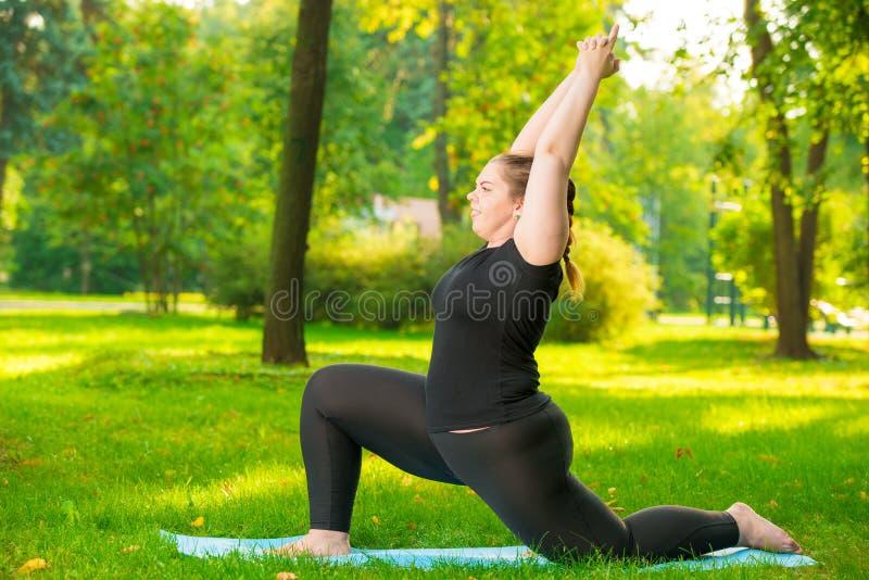 Mädchen im Park nimmt an seiner Zahl, Yogaübungen in der Frischluft teil stockfotografie
