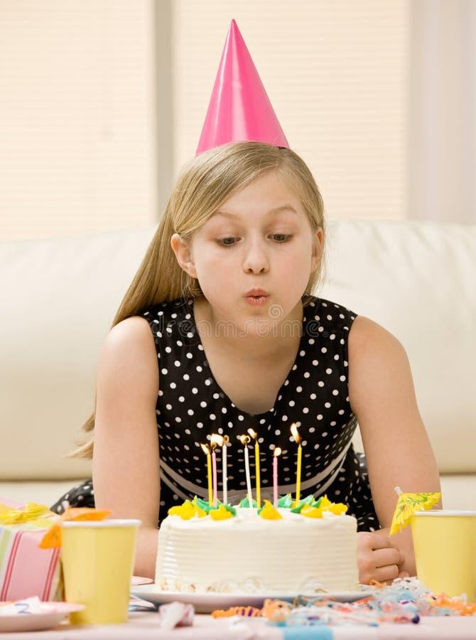 Mädchen im Partyhut, der heraus Kerzen durchbrennt stockfotos