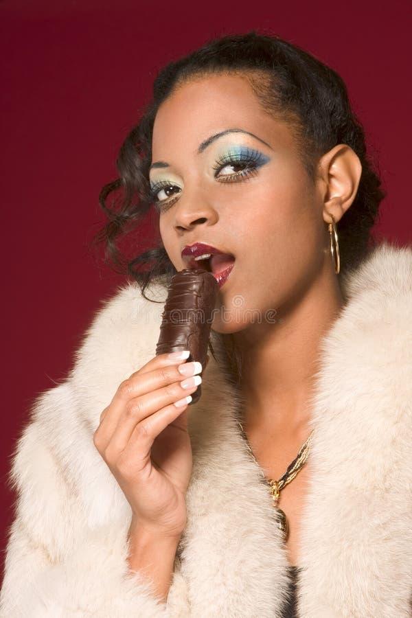Mädchen im Pelzmantel essen Schokolade lizenzfreie stockfotografie