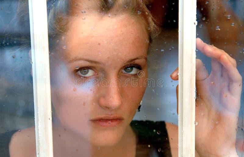 Mädchen im regnerischen Fenster stockfotografie