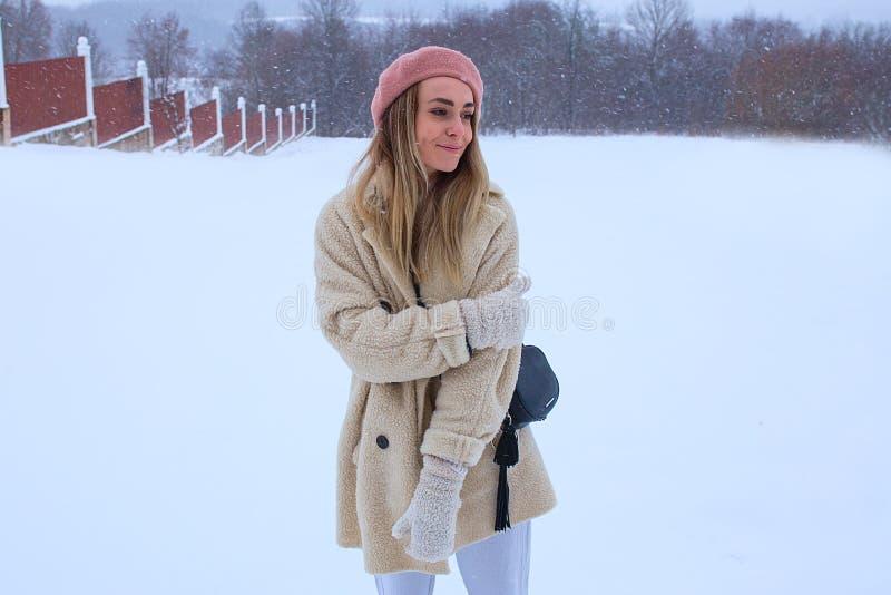 Mädchen im rosa Barett steht im Schnee und im Lächeln lizenzfreie stockbilder