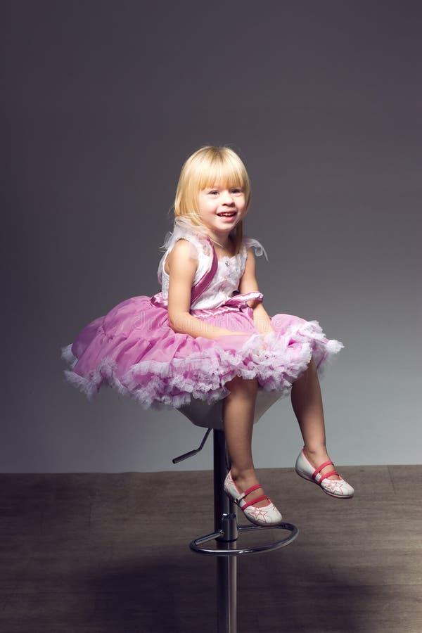 Mädchen im rosafarbenen Ballettröckchen, Studio, das einen Stuhl sitzt stockbild