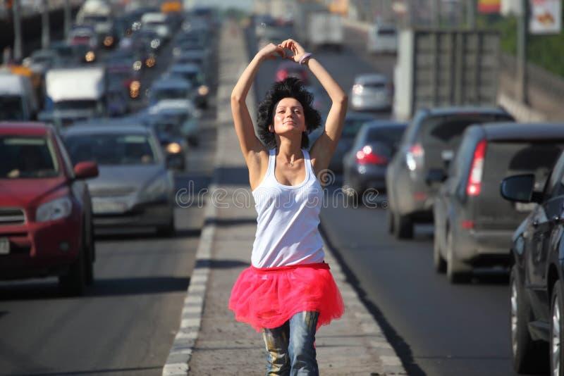 Mädchen im rosafarbenen Rock geht auf Datenbahnmitte lizenzfreies stockfoto