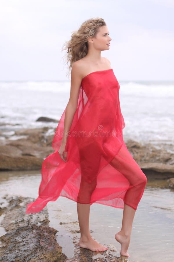 Mädchen im roten Gewebe auf einer Küste stockbilder