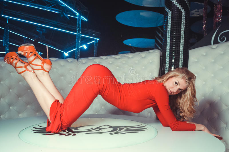Mädchen im roten Kleid auf dem Tisch lizenzfreies stockbild