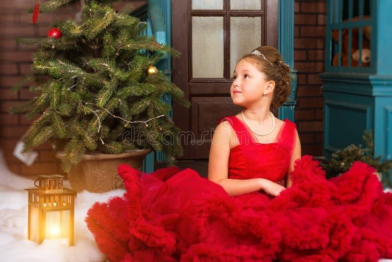 Mädchen im roten Kleid begrüßt neues Jahr und Weihnachten stockfoto