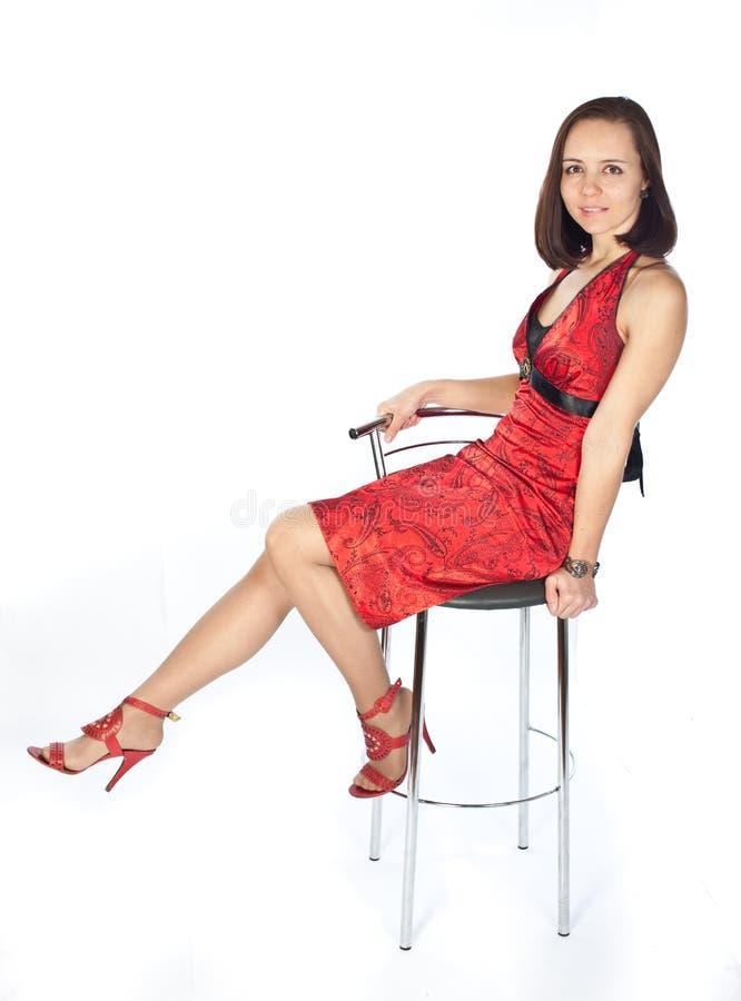 Mädchen im roten Kleid, das auf dem Stuhl sitzt lizenzfreie stockfotografie