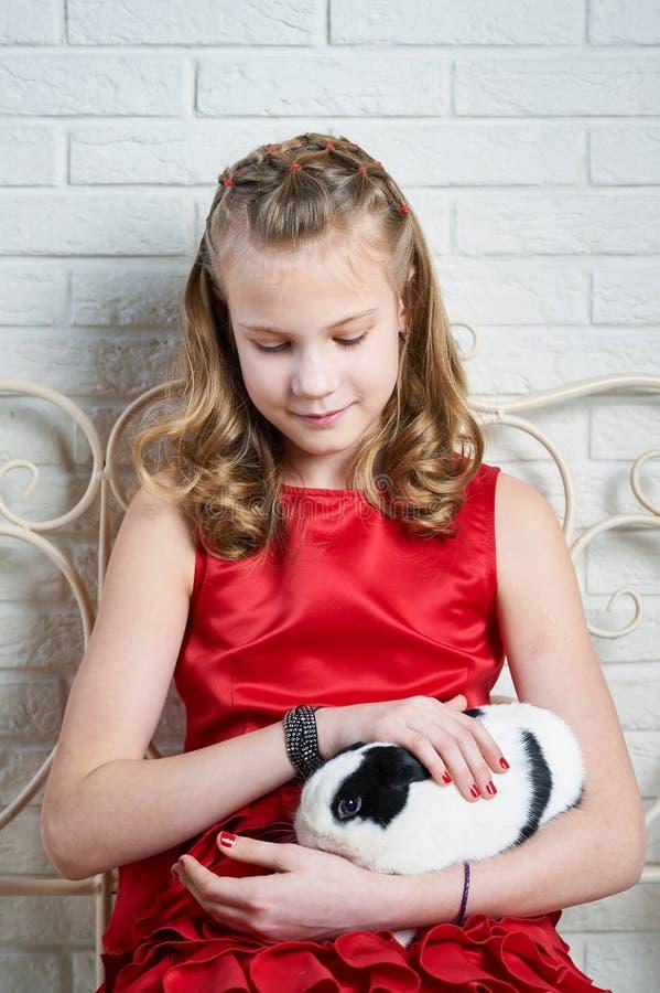 Mädchen im roten Kleid, das Kaninchen in ihren Armen hält stockfoto