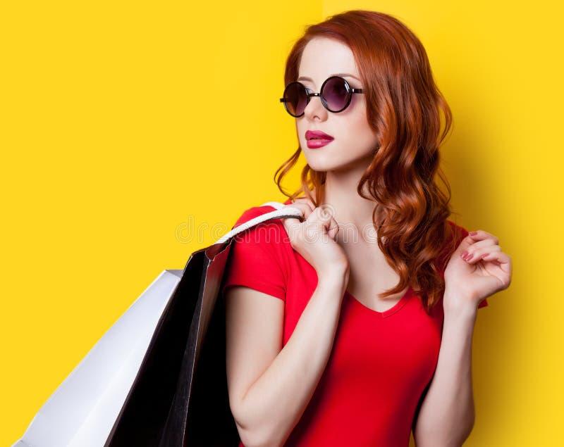 Mädchen im roten Kleid mit Einkaufstaschen lizenzfreie stockbilder
