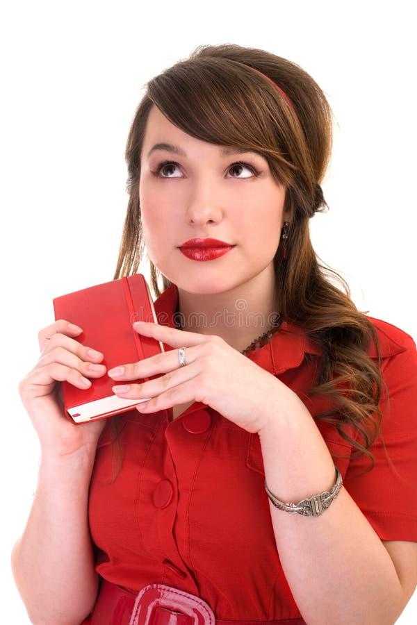 Mädchen im roten Kleid und in ihrem Tagebuch lizenzfreie stockfotografie