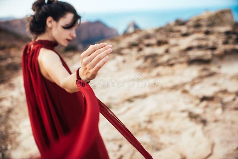 Mädchen im roten Kleid unter Felsen und Klippen entlang der Küste von Algarve stockbild