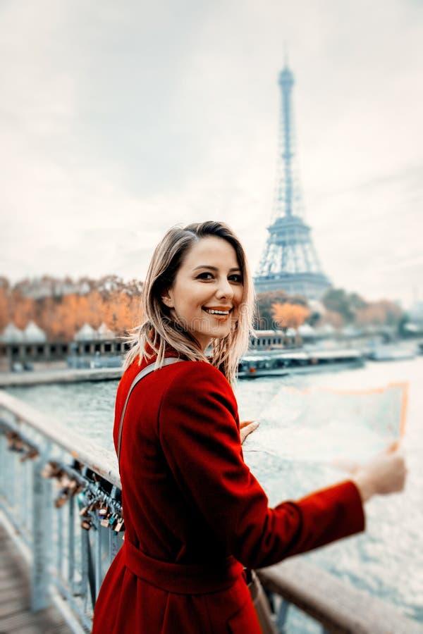 Mädchen im roten Mantel mit Karte an der Pariser Straße lizenzfreie stockfotos