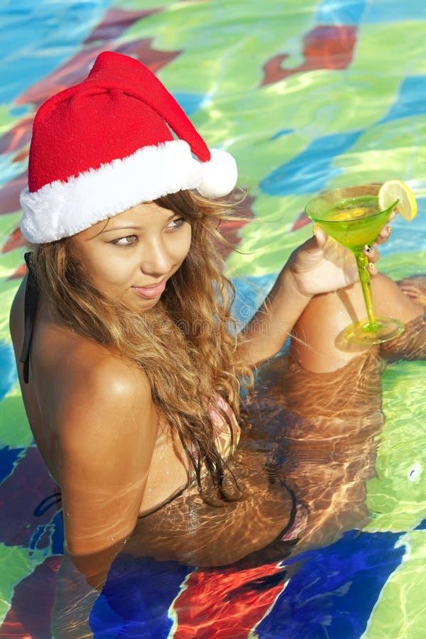 Mädchen im Sankt-Hut, der im Swimmingpool sitzt stockbilder