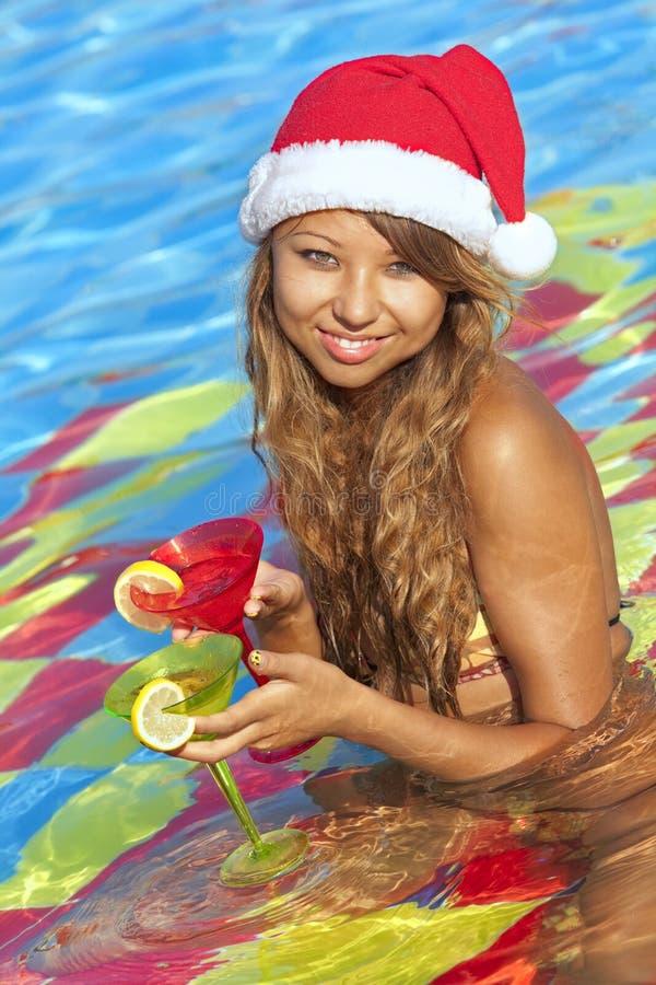 Mädchen im Sankt-Hut, der im Swimmingpool sitzt lizenzfreie stockbilder