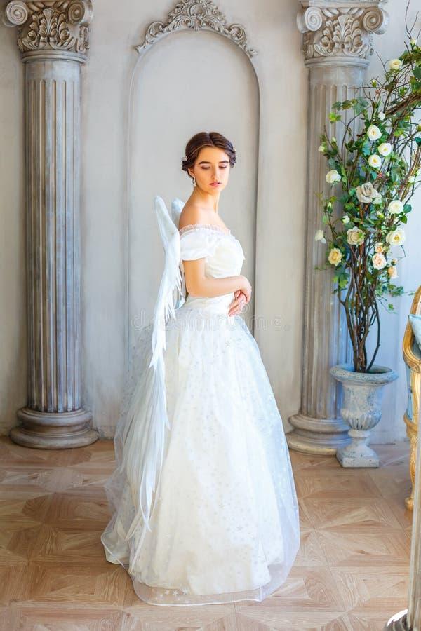 Mädchen im schönen weißen Kleid und weißen in den Flügeln, himmlisch stockfoto