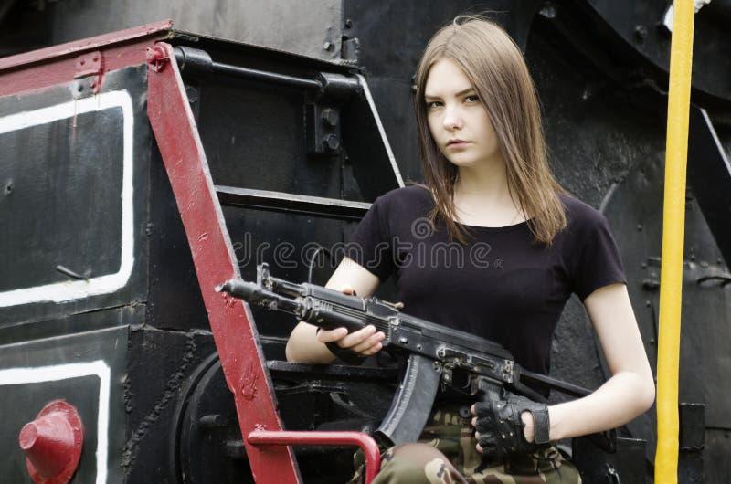 Mädchen im schwarzen T-Shirt mit einem Gewehr, werfend nahe einer Lokomotive auf lizenzfreies stockbild
